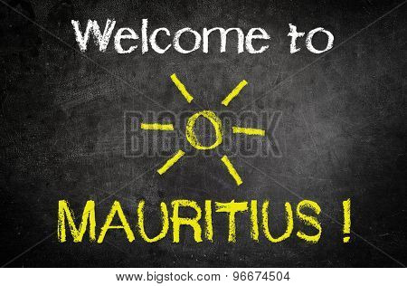 Welcome to Mauritus Message for Summer Holiday Concept Written on a Black Chalkboard with Glowing Sun Drawing in the Middle.