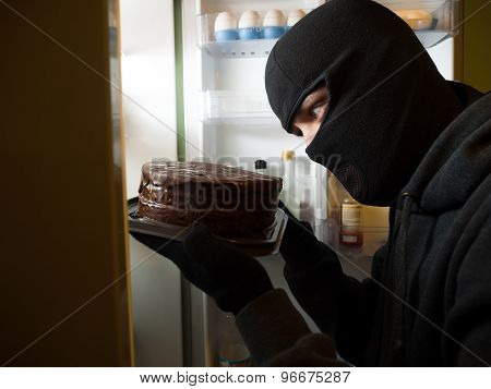 Thief. Man in black mask with a cake.