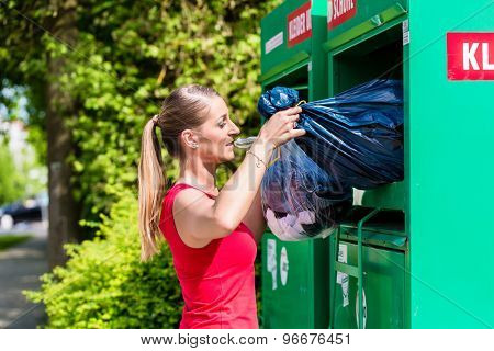 Woman at clothes recycling skip