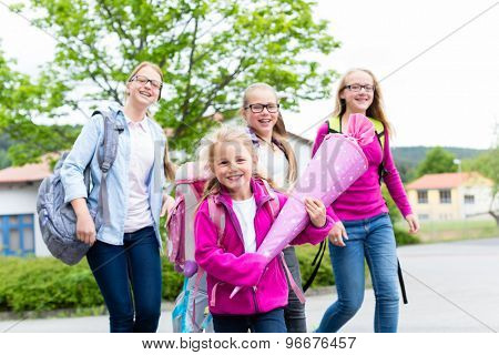 Group of students going back to school running on the schoolyard