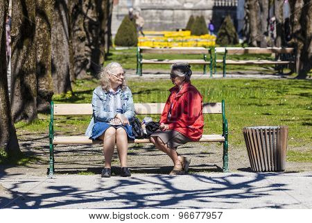 People On A Bench Relax In The Mirabell Garden