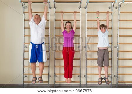 mother son and grandfather hanging on a horizontal bar in a gym