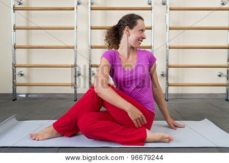 woman sitting on a rug on the floor in a gym