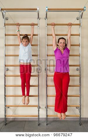 mother and daughter hanging on a horizontal bar in a gym