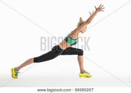 Rhythmic gymnast doing exercise in studio.
