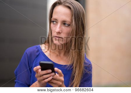 Thoughtful Woman Standing Holding Her Mobile