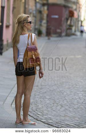 Young blondie woman in shorts and a t-shirt inspects an old European city. Travelling.