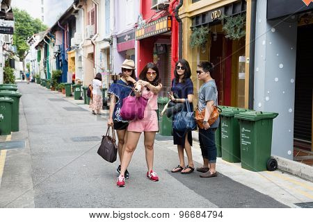 SINGAPORE - CIRCA FEBRUARY, 2015: Tourists in streets of the Arab quarter (Kampong Glam) do self. Arab Quarter is the oldest historic shopping district of Singapore, is popular for visiting tourists.
