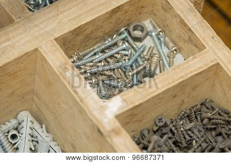 Variation of metal screws and nails placed inside a wood compartment box concept repairs, tools, han