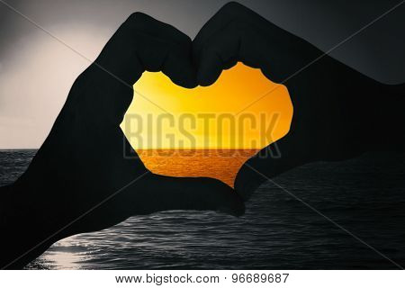 Couple making heart shape with hands against sunset of a beautiful day