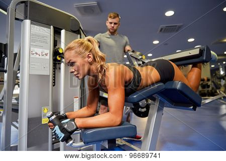 sport, fitness, bodybuilding, teamwork and people concept - young woman and personal trainer flexing muscles on leg curl machine in gym