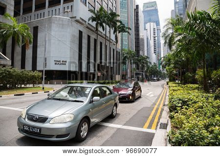 SINGAPORE - FEBRUARY 18, 2015: Cars in the Central Business District of Singapore. There are many international and national corporations and companies in the buildings.