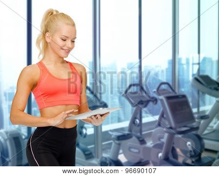 sport, fitness, technology, advertisement and people concept - smiling sporty woman with tablet pc computer over gym machines background