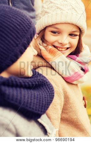 childhood, season and people concept - close up of smiling little girl and boy in autumn park
