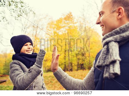 family, childhood, season, gesture and people concept - happy father and son making high five in autumn park