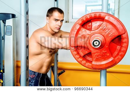Handsome muscular man with weight training equipment in a gym. Sports, bodybuilding. Healthy lifestyle.