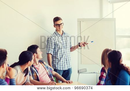 education, teamwork and people concept - smiling students with white board sitting an table indoors