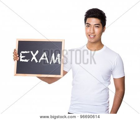 Asian man hold with chalkboard showing a word exam