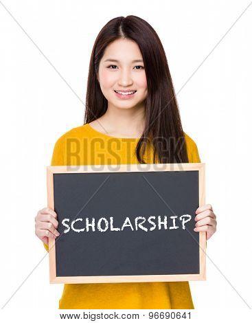 Woman hold blackboard showing a word scholarship