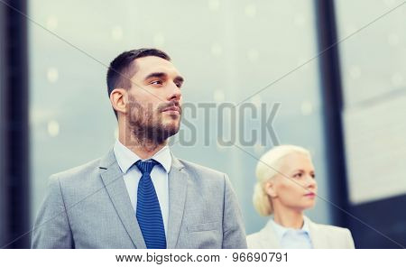 business, partnership, success and people concept - close up of serious businessman and businesswoman standing over office building