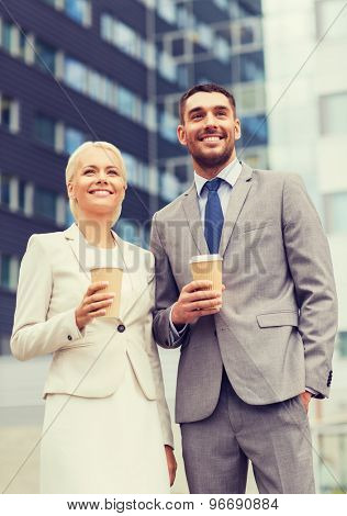 business, partnership, hot drinks and people concept - smiling businessmen with paper cups standing over office building