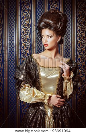 Baroque Style - beautiful young woman in elegant historical dress and with barocco hairstyle posing over vintage background. Renaissance. Barocco. Fashion.