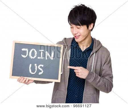 Young man finger point to chalkboard showing a phrase of join us