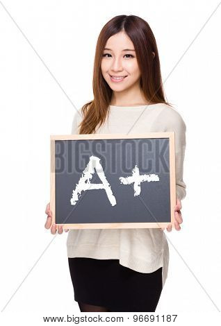 Woman hold with chalkboard showing sign of A plus