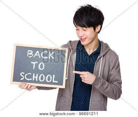 Young man finger point to chalkboard with back to scholl phrase