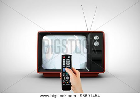 Hand holding remote control against white background with vignette
