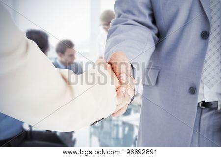 People in suit shaking hands against business people in board room meeting