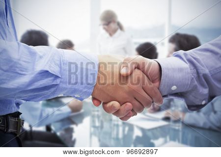 Two men shaking hands against business people in board room meeting