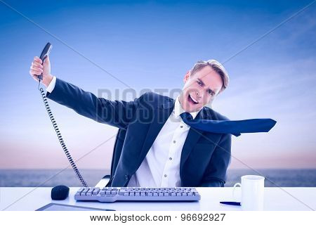 Businessman shouting as he holds out phone against beautiful sunset on a sunny day