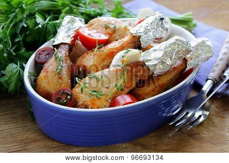 Fried chicken legs with herbs and spices, vegetables for garnish