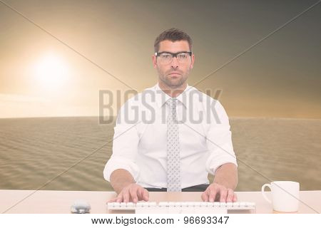 Businessman working at his desk against desert scene