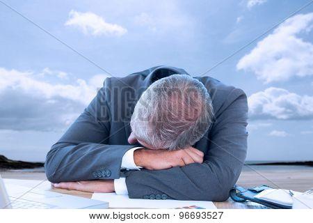 Tired businessman resting on desk against beach