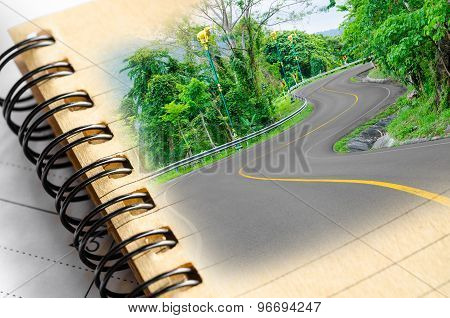 S-curved Road To Mountain With Blank Diary.
