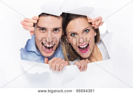 Couple peeping through hole on paper