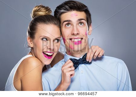 Man with lipstick marks and smiling woman
