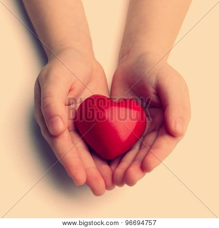 Heart in child hands on light background