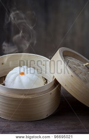 Chinese Steamed Bun In Bamboo Ware On Wooden Table