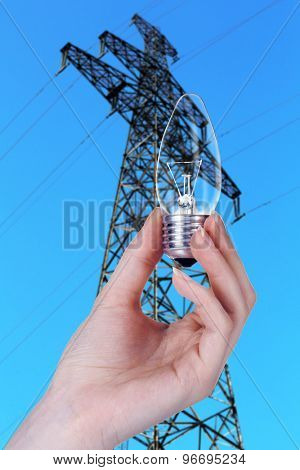 Light bulb in hand on high voltage line background