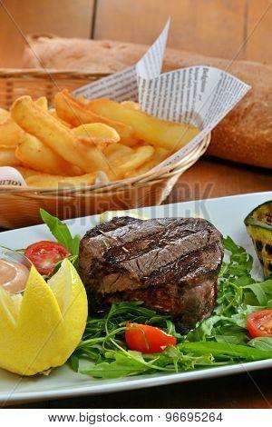 Beef steak mediun grilled on salad dish and potatoes fries.