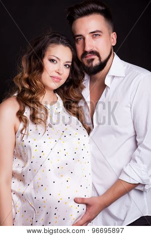 Beautiful Couple And Pregnant Woman Over Black Background