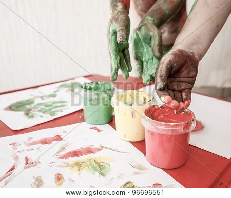 Children Dipping Fingers In Washable Finger Paints