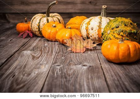 Autumn still life with pumpkins and leaves on old wooden background