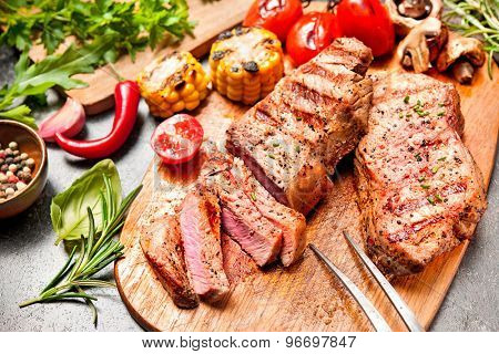 Grilled veal steaks with vegetables on cutting board