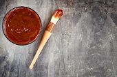 picture of baste  - Barbecue sauce with basting brush over stone table with room for copy space - JPG