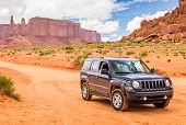 Постер, плакат: Monument Valley Utah Usa May 25 2015 Offroading Through The Monument Valley In A Jeep Patriot