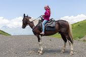 foto of mountain chain  - girl sitting on a horse in the mountains - JPG